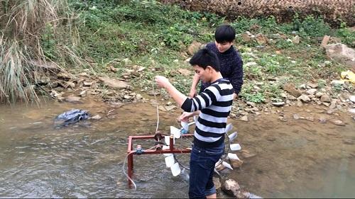 Hai nhà phát minh đang thử chạy thiết bị đưa nước lên cao không cần dùng điện tại một con suối.